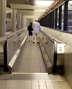 Man and teenage girl on airport moving walkway